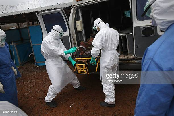 A burial team unloads an Ebola victim who died in an ambulance while collecting him for cremation on October 2 2014 in Monrovia Liberia Eight...