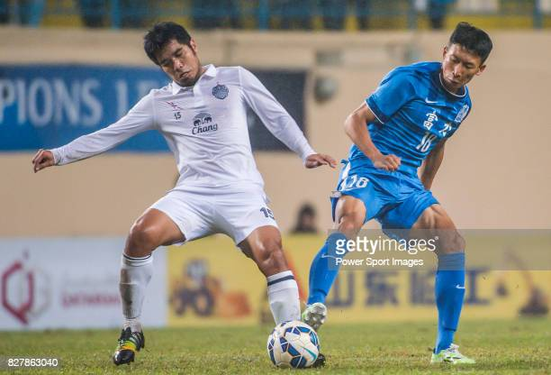 Buriram United midfielder Surat Sukha fights for the ball with Guangzhou RF midfielder Zhang Yuan during the AFC Champions League 2015 Group Stage F...