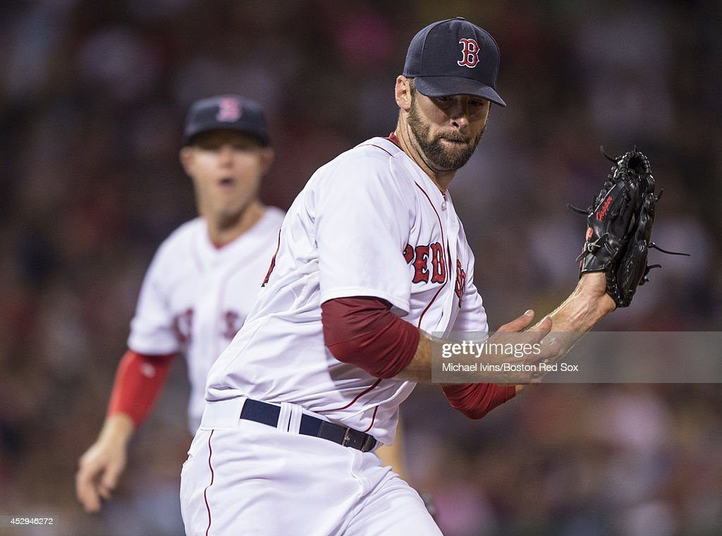 Burke Badenhop #35 of the Boston Red Sox tags first base against the Toronto Blue Jays in the eighth inning on July 30, 2014 at Fenway Park in Boston, Massachusetts. Photo by Michael Ivins/Boston Red Sox/Getty Images)