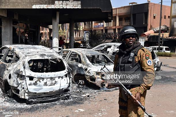 A Burkina Faso gendarme stands guard next to burnt cars outside Splendid Hotel in Ouagadougou on January 18 2016 following a jihadist attack by...