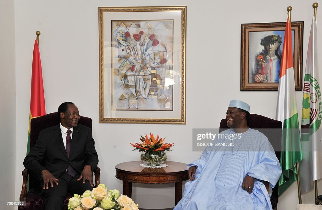 Burkina Faso president Blaise Compaore and Ivory Coast president Alassane Ouattara laugh during a meeting on March 4, 2014 at the president's residence in Abidjan. Burkina Faso's president Compaore is on a one-day visit to the western African country.