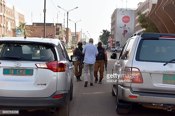 Burkina Faso troops speak with an unidentified diplomat near the Splendid hotel and the Cappuccino restaurant following a jihadist attack in...