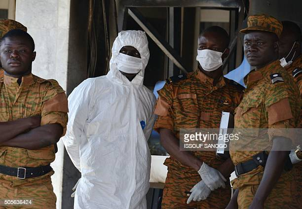 Burkina Faso troops stand next to a forensics expert at the entrance of Splendid Hotel in Ouagadougou on January 18 2016 following a jihadist attack...