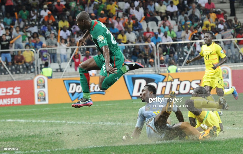 Burkina Faso's midfielder Prejuce Nakoulma (L) and Togo's goalkeeper Kossi Agassa (C) look at the ball during the African Cup of Nation 2013 quarter final football match Burkina Faso vsTogo, on February 3, 2013 in Nelspruit.