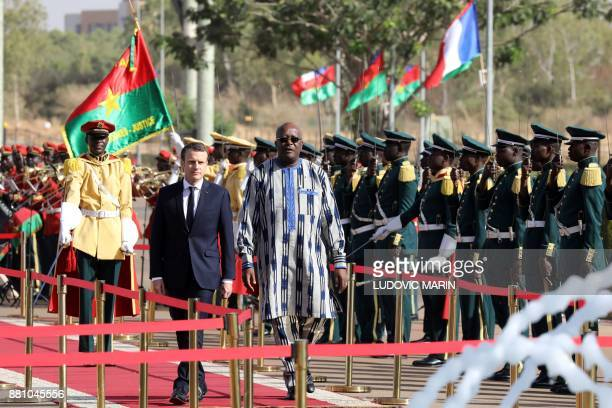 Burkina Faso's President Roch Marc Christian Kabore and French President Emmanuel Macron review troops during a welcoming ceremony at the...