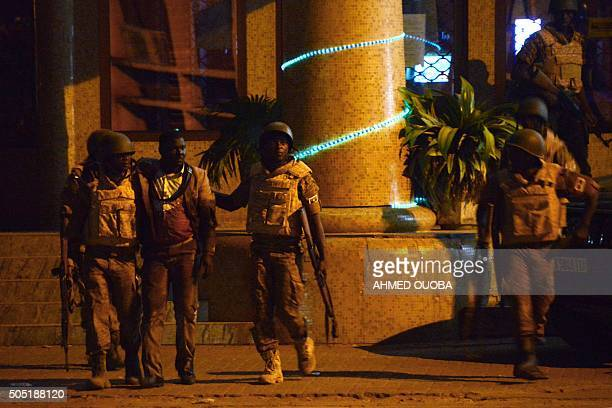 TOPSHOT Burkina Faso's soldiers evacuate an injured man from the Splendid hotel during an attack on both the hotel and a restaurant by AlQaeda linked...