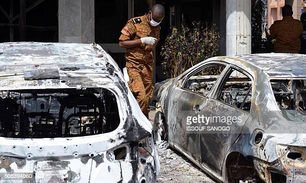 Burkinabe investigator walks next to burnt cars in front of the Splendid hotel on January 17 2016 in Ouagadougou following a jihadist attack claimed...