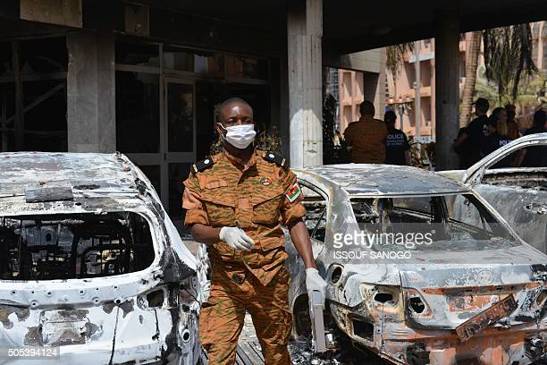 A Burkinabe investigator walks next to burnt cars in front of the Splendid hotel on January 17 2016 in Ouagadougou following a jihadist attack...
