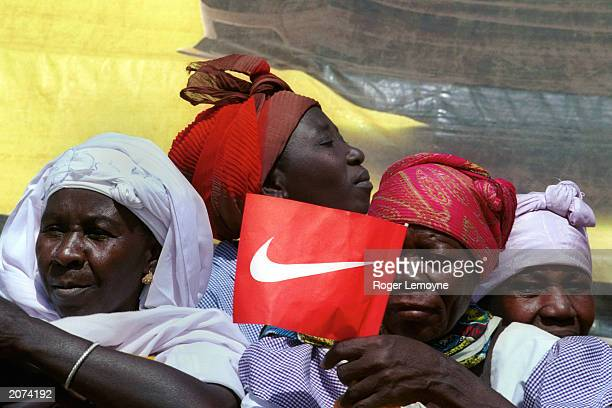 Burkinabe women spectators wave free Nike flags at the finish line of a stage of the Tour Du Faso November 8 2001 in Burkina Faso Corporate...