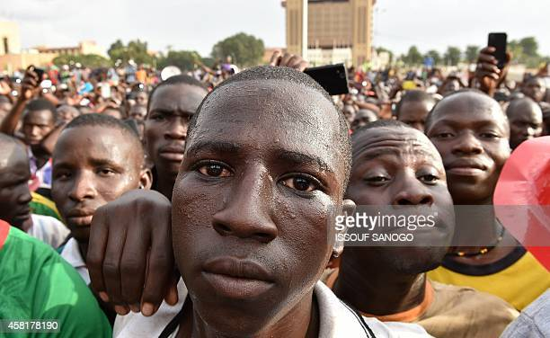Burkinese people listen to a lieutenantcolonel reading a press release by the army chief after the resignation of Burkina Faso's president in...