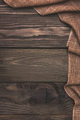 Brown burlap cloth on an old wooden background. Top view, space for text