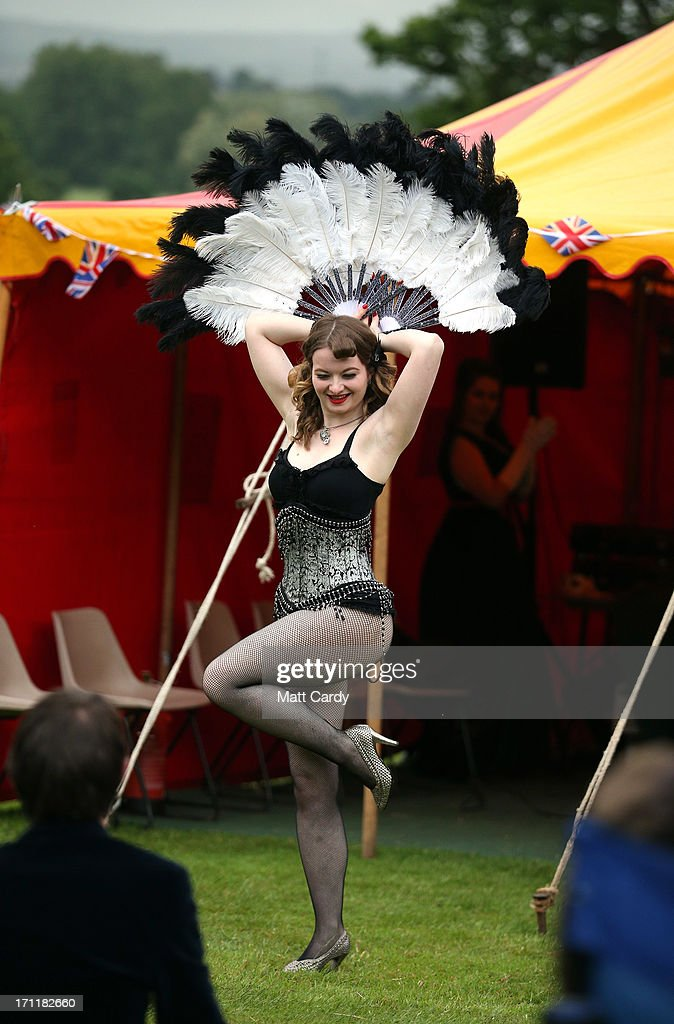 A burlesque dancer performs in the gardens at Killerton House on June 22, 2013 in Exeter, England. The National Trust property, near Exeter, is holding a two day vintage weekend with stalls selling vintage fashion, home ware and crafts, displays of classic cars and features an evening of entertainment which includes burlesque dancers.