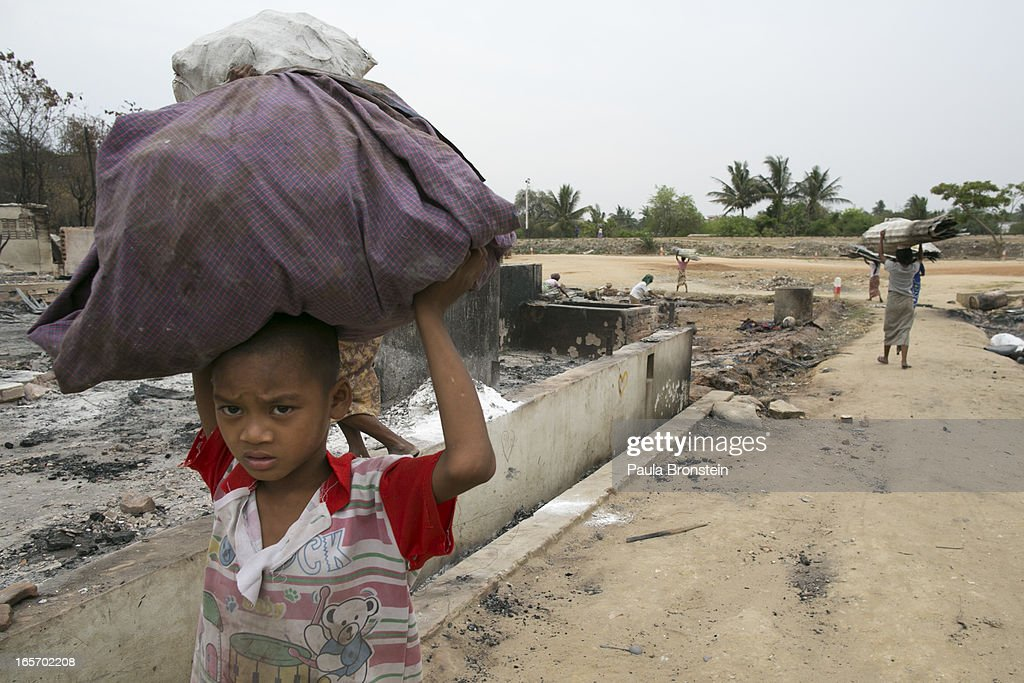 A Burmese boy carries items salvaged from destroyed buildings April 5, 2012 in Meiktila, Myanmar. Recent sectarian violence between Buddhists and Muslims in March left 43 people dead, with large areas of the town completely destroyed by fires and looting, while many were injured with thousands of Muslim now homeless. Many Muslims who had money fled as the violence after began to spin out of control while the remaining people are being kept in well policed IDP camps in the town.