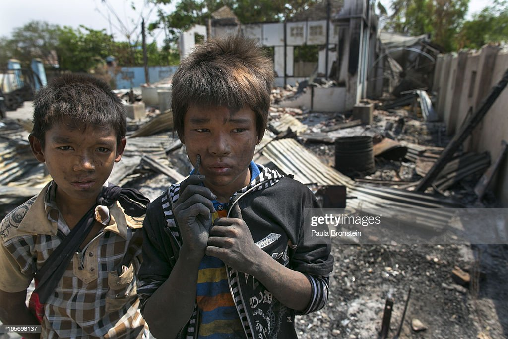 Burmese boys stand near their destroyed home covered with charcoal on April 5, 2012 in Meiktila, Myanmar. Recent sectarian violence between Buddhists and Muslims in March left 43 people dead, with large areas of the town completely destroyed by fires and looting, while many were injured with thousands of Muslim now homeless. Many Muslims who had money fled as the violence after began to spin out of control while the remaining people are being kept in well policed IDP camps in the town.