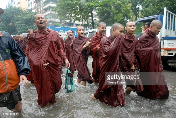 Burmese Buddhist monks protesting against the military junta are marching in a street of Rangoon flooded by heavy monsoon rain