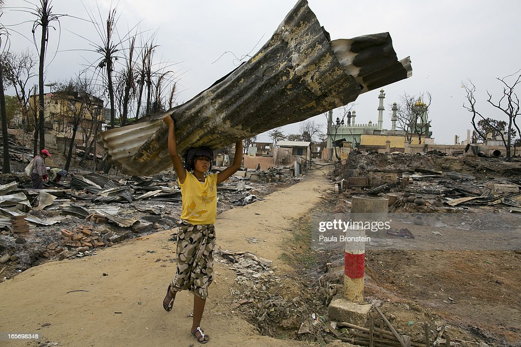 A Burmese carries away a burned tin roof from the devastation on April 5, 2012 in Meiktila, Myanmar. Recent sectarian violence between Buddhists and Muslims in March left 43 people dead, with large areas of the town completely destroyed by fires and looting, while many were injured with thousands of Muslim now homeless. Many Muslims who had money fled as the violence after began to spin out of control while the remaining people are being kept in well policed IDP camps in the town.