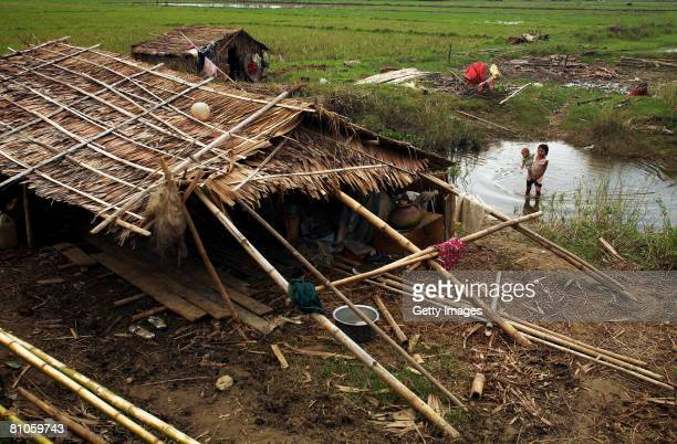 Burmese child holds an infant in a pond beside a damaged house after Cyclone Nargis struck last week on May 12 in Maubin Myanmar It has been...