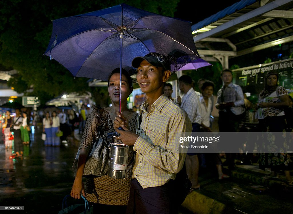 A Burmese couple stands in the rain waiting at a bus stop November 30, 2012 in Yangon, Myanmar. Business is booming in this newly opened Southeast Asian country. Import restrictions have been eased resulting in many new cars seen on the streets.