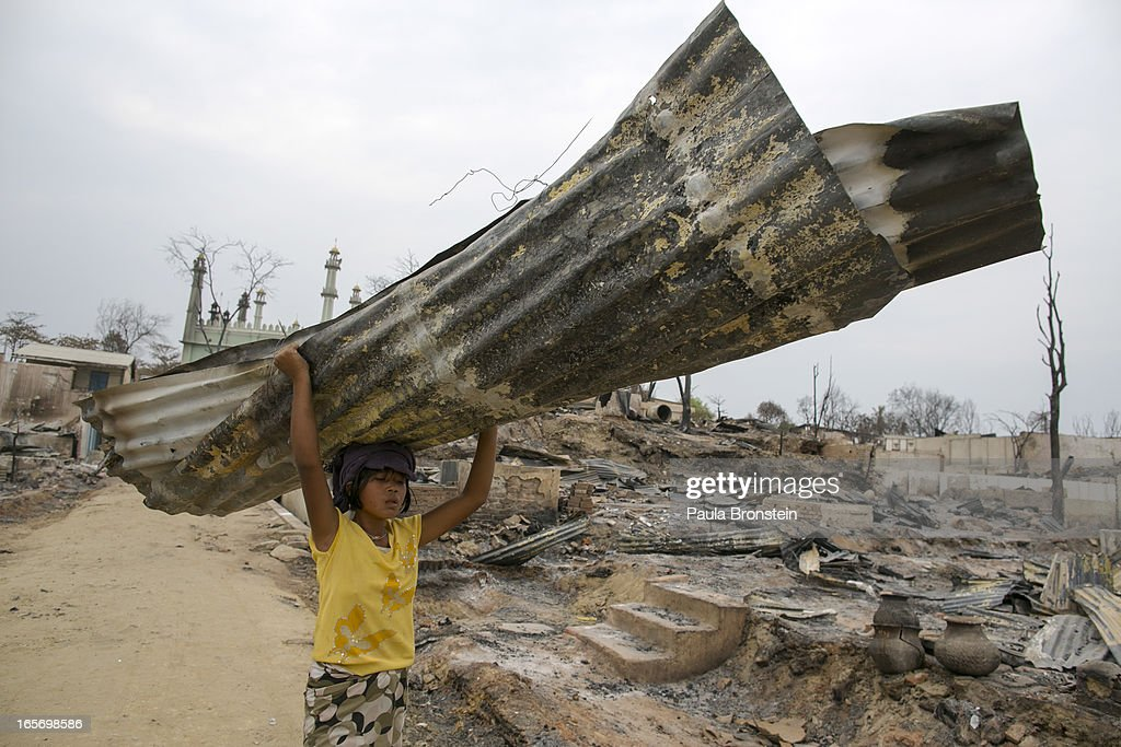 A Burmese girl carries away a burned tin roof from devastated buildings on April 5, 2012 in Meiktila, Myanmar. Recent sectarian violence between Buddhists and Muslims in March left 43 people dead, with large areas of the town completely destroyed by fires and looting, while many were injured with thousands of Muslim now homeless. Many Muslims who had money fled as the violence after began to spin out of control while the remaining people are being kept in well policed IDP camps in the town.