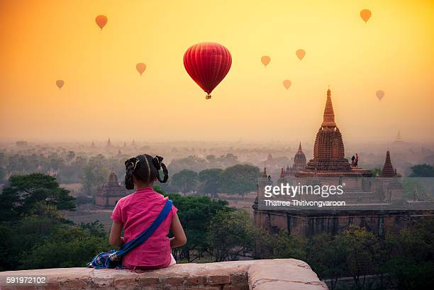Burmese girl with traditional thanaka on her face praying on pagoda blurred background at bagan in Mandalay, Myanmar