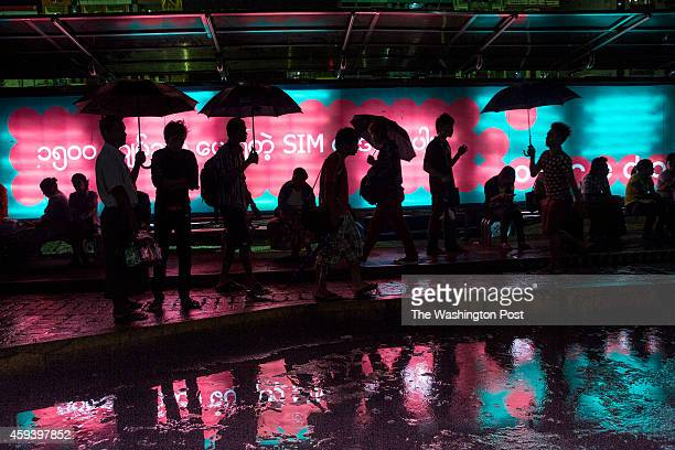 Burmese hold umbrellas at a bus stop during a rainstorm next to a huge Ooredoo billboard in Yangon Ooredoo and Telenor are the two new 3G GSM...