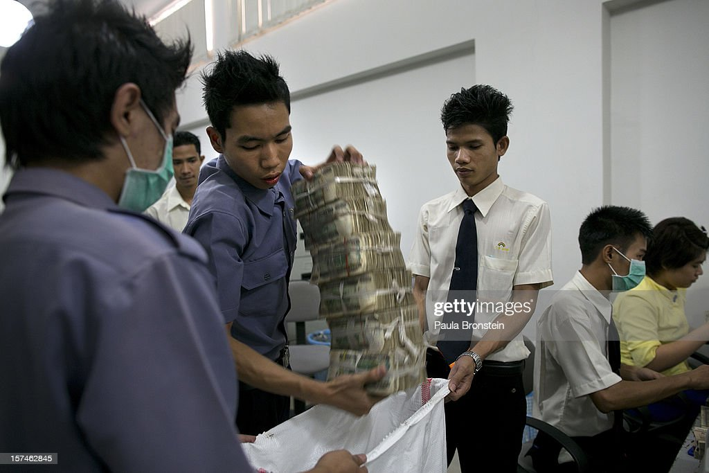 Burmese Kyat is put into a money bag after being counted at a bank November 30, 2012 in downtown Yangon, Myanmar. Burmese kyat is now available at ATM machines for the first time. Business is booming in this newly opened Southeast Asian country. Import restrictions have been eased resulting in many new cars seen on the streets.