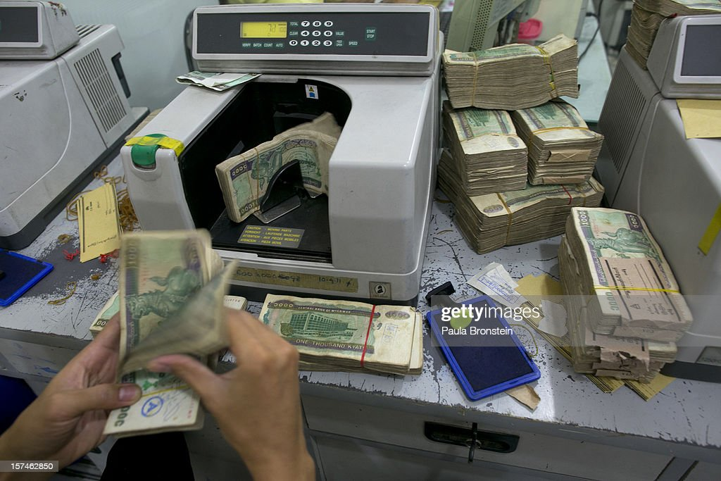 Burmese Kyat is seen being counted at a bank November 30, 2012 in downtown Yangon, Myanmar. Burmese kyat is now available at ATM machines for the first time. Business is booming in this newly opened Southeast Asian country. Import restrictions have been eased resulting in many new cars seen on the streets.