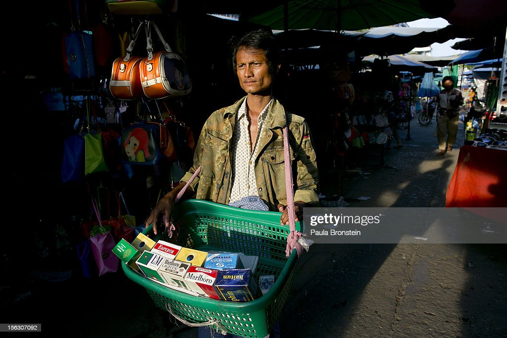 A Burmese man sells cigarettes at duty free prices at an outdoor market selling counterfeit Chinese made items in the Golden Triangle, situated along the Thai- Burma border on November 12, 2012 in Tachiliek, Myanmar. Chinese copies boasting well known brands flood this market allowing Thai shoppers and tourists to travel over the border to buy everything from fake iPhones, designer purses, watches and sunglasses.