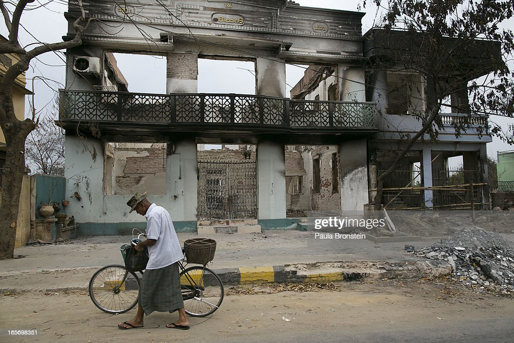 A Burmese man walks by destroyed buildings on April 5, 2012 in Meiktila, Myanmar. Recent sectarian violence between Buddhists and Muslims in March left 43 people dead, with large areas of the town completely destroyed by fires and looting, while many were injured with thousands of Muslim now homeless. Many Muslims who had money fled as the violence after began to spin out of control while the remaining people are being kept in well policed IDP camps in the town.