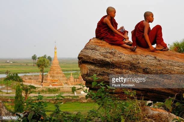 Burmese monks sit on a huge fallen tree from Cyclone Nargis April 20 2009 in the Irrawady delta village of Kungyangon Myanmar Life has basically...