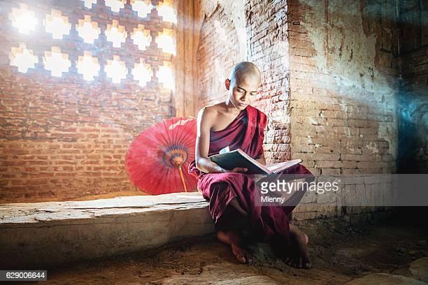 Burmese Novice Buddhist Monk in Temple Reading Bagan Myanmar
