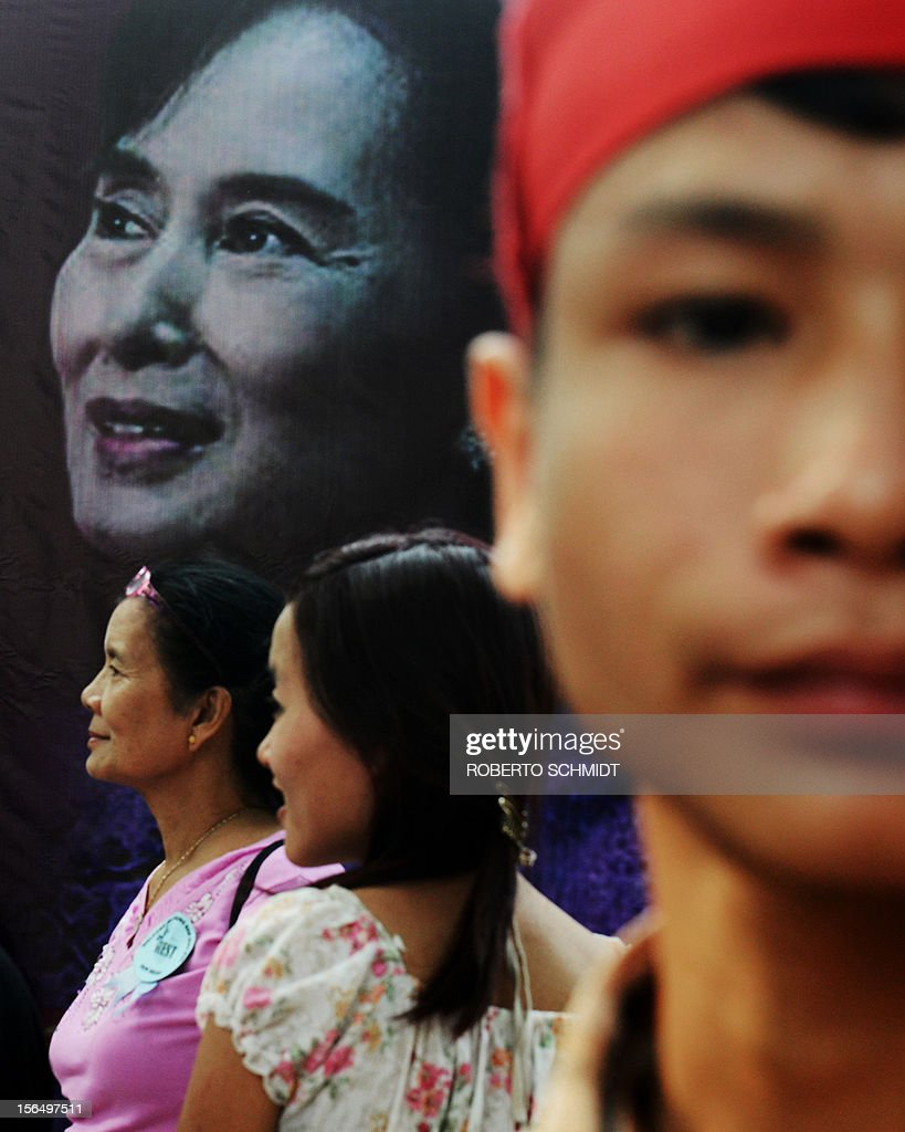Burmese people living in New Delhi gather near a poster bearing the portrait of Myanmar opposition leader and National League for Democracy Chairperson Aung San Suu Kyi near the entrance of a school in New Delhi on November 16, 2012. The Nobel laureate, on a visit to neighbouring India and who is now a member of parliament after dramatic changes overseen by a quasi-civilian regime that took power last year, was released from military house arrest in 2010. AFP PHOTO/Roberto Schmidt