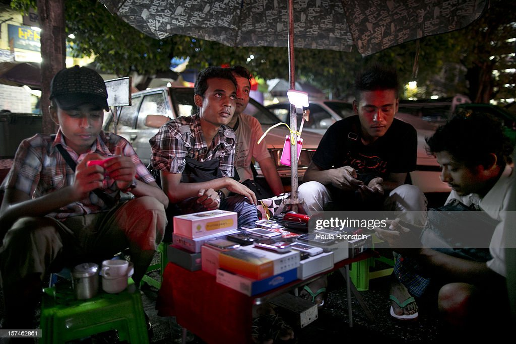 Burmese play with their mobile phones as a used phone dealer wait for business at a street market November 30, 2012 in Yangon, Myanmar. Business is booming in this newly opened Southeast Asian country. Import restrictions have been eased resulting in many new cars seen on the streets.