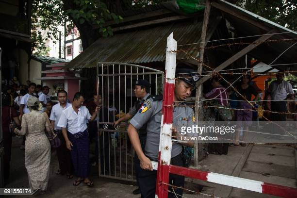 Burmese police officer carries a barbed wire fence into the courthouse compound to block access to the trial of three Buddhist nationalists on June 2...