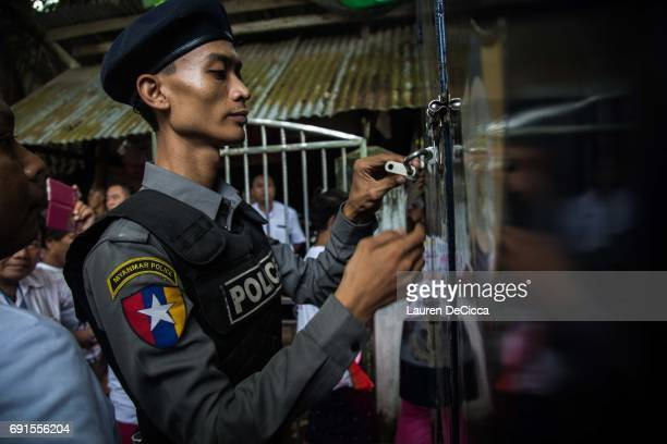 Burmese police officer locks the police van after the trial of three Buddhist nationalists on June 2 2017 in Yangon Burma Buddhist hardliners like...