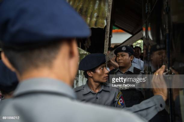 Burmese police officers keep watch outside of the courthouse compound to block access to the trial of three Buddhist nationalists on June 2 2017 in...