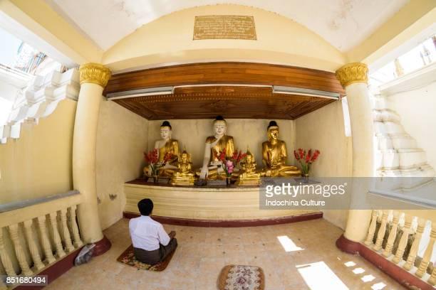 Burmese praying in front of Statues of Buddha in Shwedagon Pagoda, Yangon, Myanmar