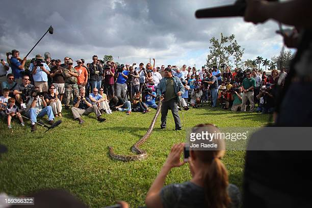 Burmese python is held by Jeff Fobb as he speaks to hunters and the media at the registration event and press conference for the start of the 2013...