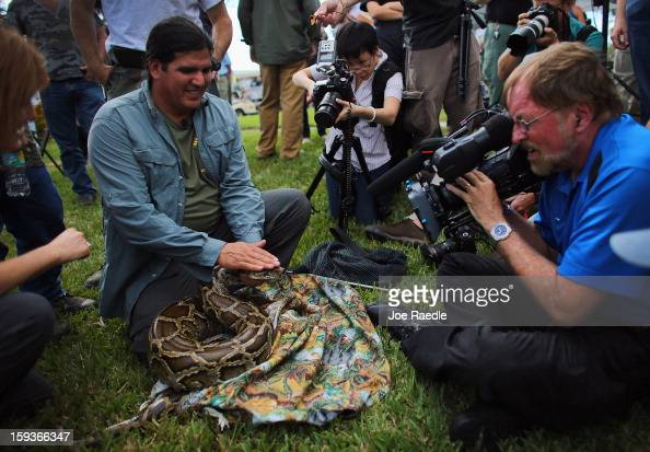 Burmese python is held by Jeff Fobb as he speaks to the media at the registration event and press conference for the start of the 2013 Python...