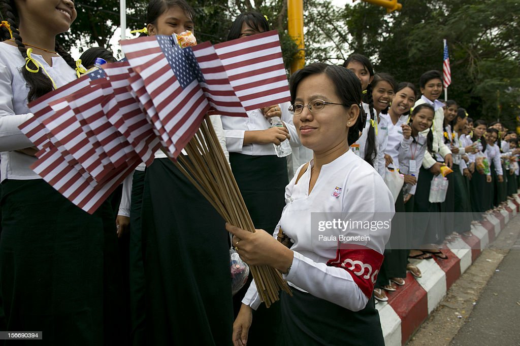 A Burmese teacher holds American flags as students line the streets to welcome US President Barack Obama as arrives at Yangon International airport during his historical first visit to the country on November 19, 2012 in Yangon, Myanmar. Obama is the first US President to visit Myanmar while on a four-day tour of Southeast Asia that also includes Thailand and Cambodia.