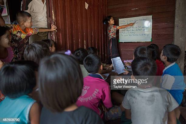 Burmese teacher instructs students in a small classroom in a village near the planned Dawei SEZ on August 2 2015 in Bawar Village Myanmar The...