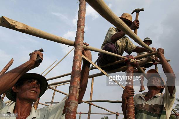 Burmese villagers help build a new house for a family who lost their home during cyclone Nargis April 26 2009 in the Irrawaddy delta village of Pale...