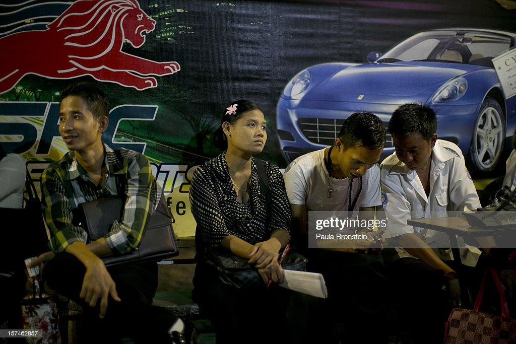 Burmese wait at a bus stop after work next to advertisements about new cars November 30, 2012 in Yangon, Myanmar. Business is booming in this newly opened Southeast Asian country. Import restrictions have been eased resulting in many new cars seen on the streets.
