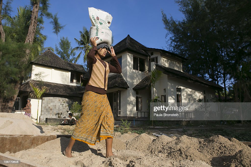A Burmese woman carries cement working at a construction site of a new resort November 28, 2012 on Ngapali beach, Myanmar. Myanmar possesses great tourist potential and the country's tourism industry is developing fast. Ngapali beach, along the Andaman Sea, is considered the top beach resort with much of the surrounding area still remaining to be developed. Investment opportunities are growing every day as real estate prices increase with investor demand.