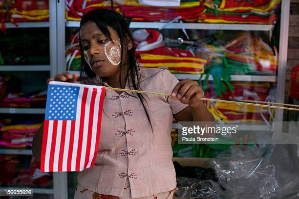 Burmese woman fixes an American flag onto a wooden stick at a flag shop as Yangon gets prepared for the first visit of President Barack Obama...