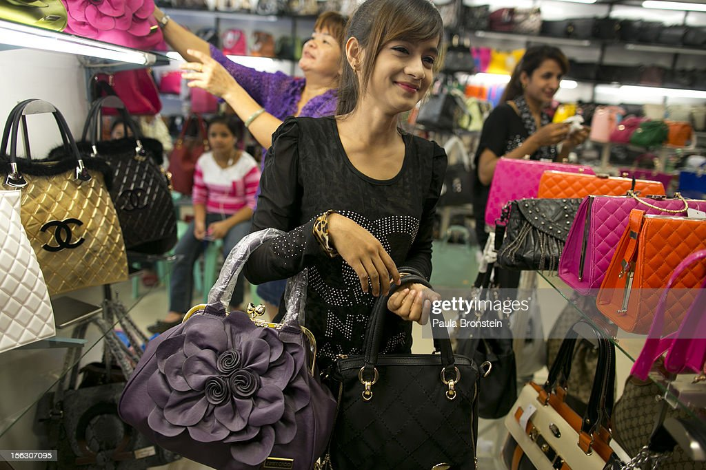 A Burmese woman holds counterfeit Chinese made luxury brand ladies bags at an outdoor market in the Golden Triangle, situated along the Thai- Burma border on November 12, 2012 in Tachiliek, Myanmar. Chinese copies boasting well known brands flood this market allowing Thai shoppers and tourists to travel over the border to buy everything from fake iPhones, designer purses, watches and sunglasses.