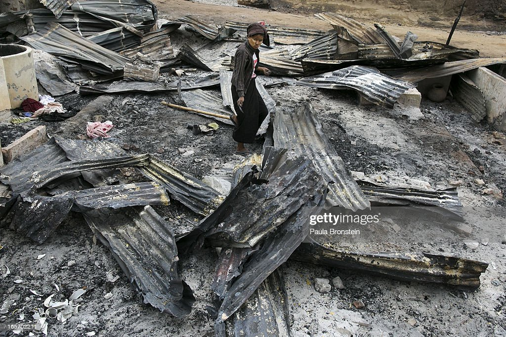 Burmese woman looks for anything to salvage among debris left by a fire on April 5, 2012 in Meiktila, Myanmar. Recent sectarian violence between Buddhists and Muslims in March left 43 people dead, with large areas of the town completely destroyed by fires and looting, while many were injured with thousands of Muslim now homeless. Many Muslims who had money fled as the violence after began to spin out of control while the remaining people are being kept in well policed IDP camps in the town.