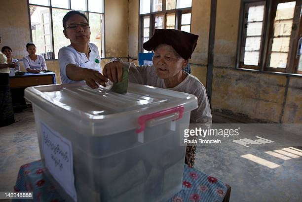 Burmese woman recieves help putting her ballot in the box as she votes in the parliamentary elections on April 1 in Kaw Hmu Myanmar Aung San Suu Kyi...