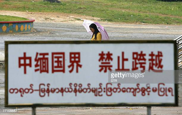 Burmese woman walks hehind a warning sign standed along the boundary line in the ChinaMyanmar border town of Wanding in China's southwestern province...