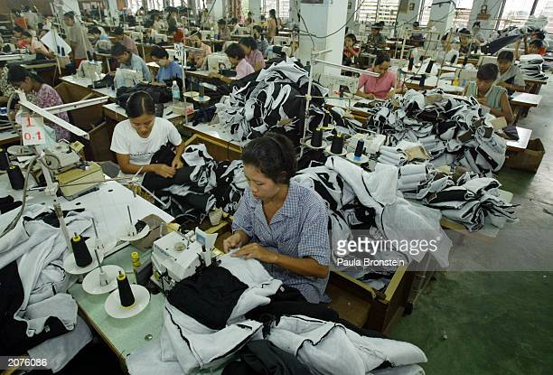 Burmese women stitch sports clothing in a garment factory for a Taiwanese company June 12 2003 in Hlaing Tharyar Myanmar They make an average wage of...